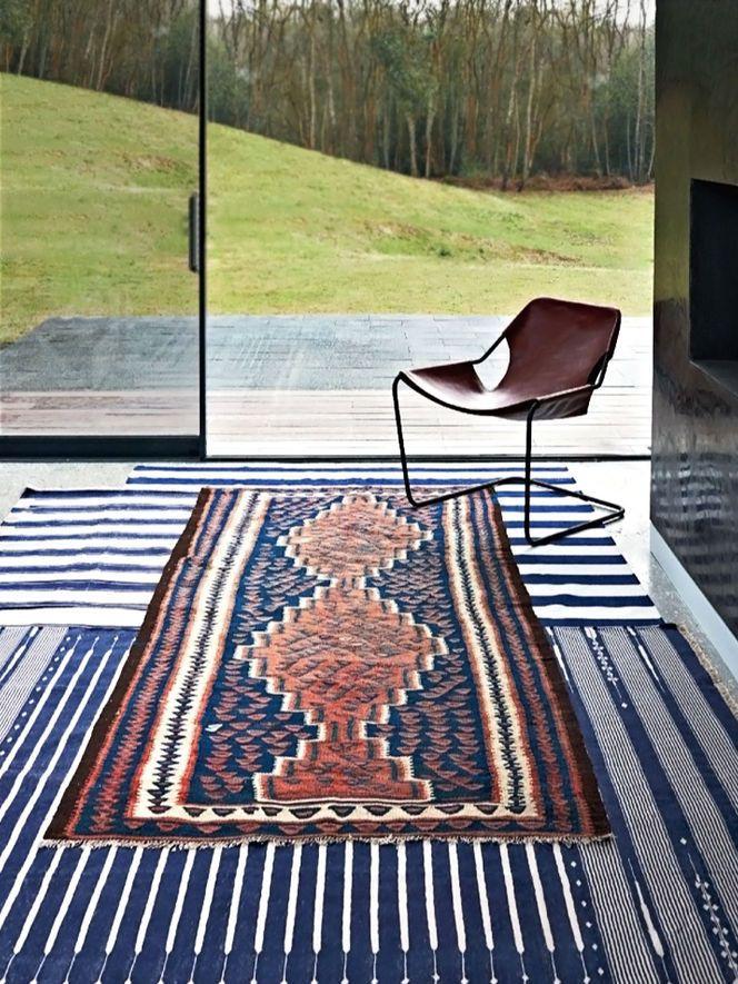 Sobreposição de tapetes em tom azul e marsala